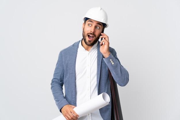 ヘルメットと誰かと携帯電話との会話を維持する白い壁に分離された青写真を保持している若い建築家男