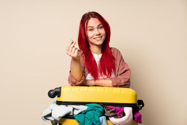 お金のジェスチャーを作るベージュの壁に分離された服の完全なスーツケースを持つ旅行者女性