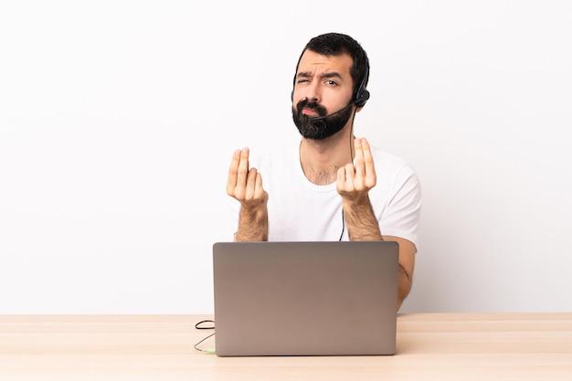 ヘッドセットとお金のジェスチャーを作るラップトップで働いているが台無しにされているテレマーケティング白人男