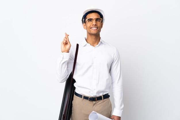 Афро-американский архитектор человек со шлемом и держа чертежи над изолированной белой стеной с пальцами, пересекающими
