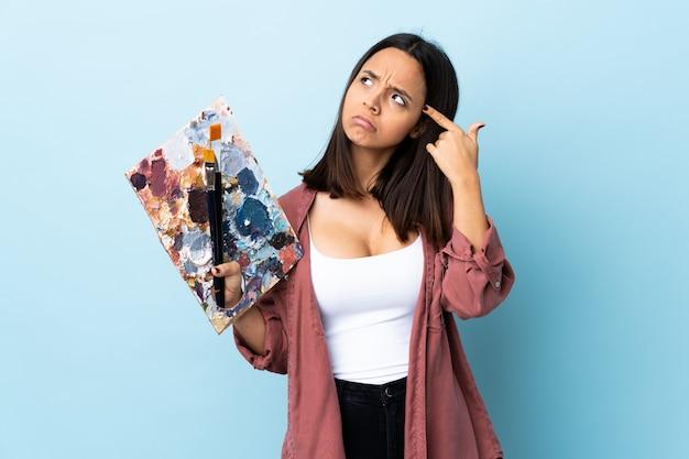 若いアーティストの女性が頭の上に指を置く狂気のジェスチャーを作る孤立した青い壁の上にパレットを保持