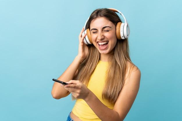 Молодая женщина над изолированной синей стеной прослушивания музыки с мобильного телефона и пения