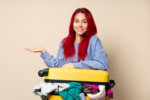 に向かって笑顔を見ながらアイデアを提示するベージュの壁に分離された服の完全なスーツケースを持つ旅行者女性