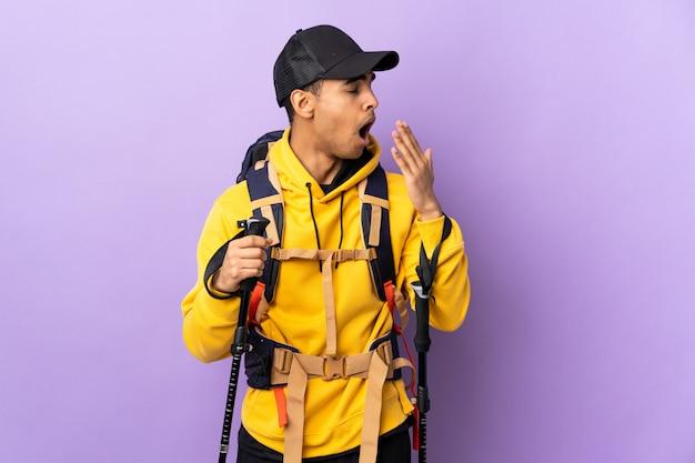 Афро-американский мужчина с рюкзаком и треккинговыми палками над изолированной стеной, зевая и прикрывая широко открытый рот рукой