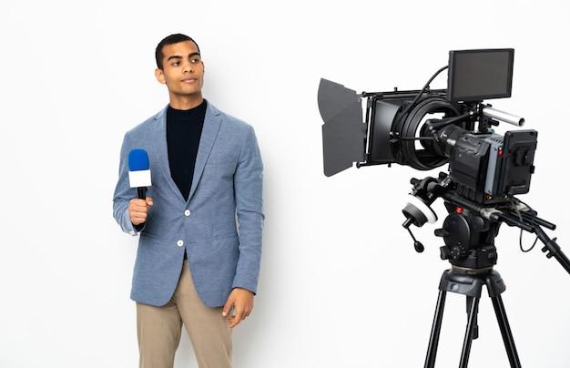マイクを押しながら側を見ながら疑問を持つ孤立した白い壁にニュースを報告するアフリカ系アメリカ人記者