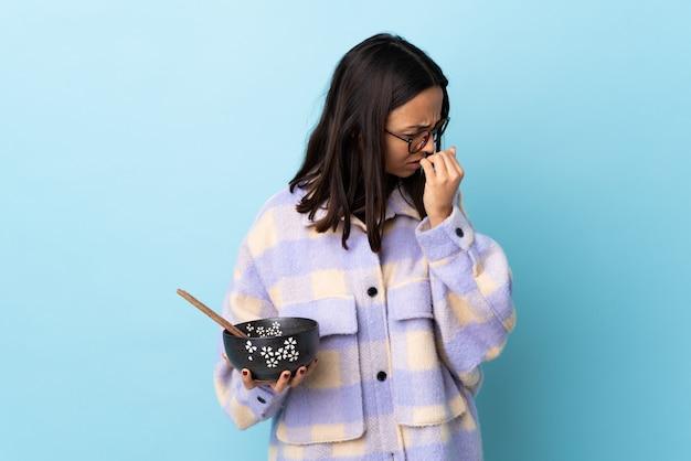Молодая брюнетка смешанной расы женщина держит миску с лапшой над синей стеной, имея сомнения