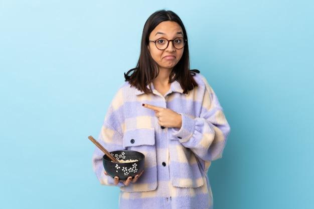 Молодая брюнетка смешанной расы женщина держит миску с лапшой над изолированной синей стеной, указывая на боковые стороны, имеющие сомнения