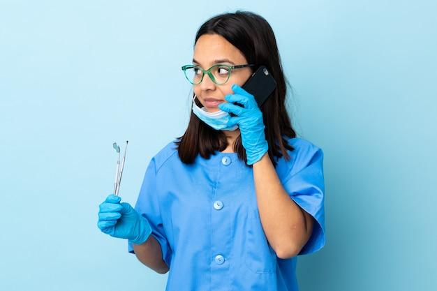 Молодая брюнетка смешанной расы стоматолог женщина держит инструменты над изолированной стеной, сохраняя разговор с мобильным телефоном с кем-то