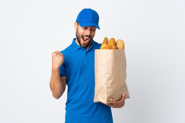勝利を祝っている白い壁に分離されたパンの完全な袋を保持している配達人