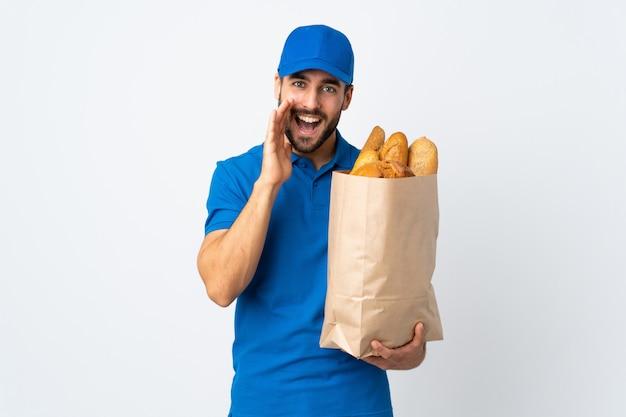 口を大きく開いて叫んでいる白い壁に分離されたパンの完全な袋を保持している配達人