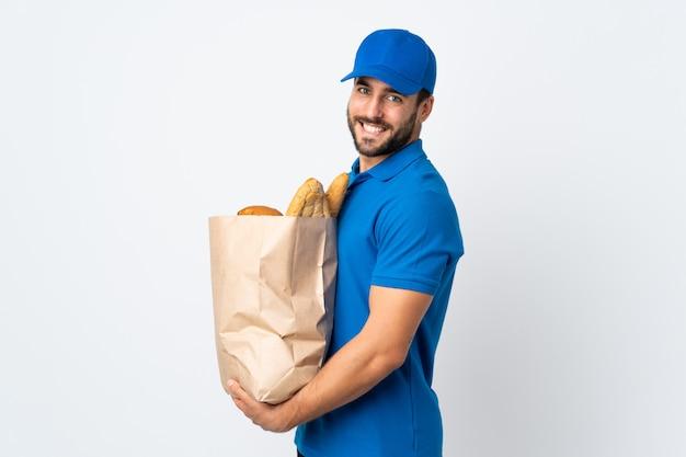 多くの笑みを浮かべて白い壁に分離されたパンの完全な袋を保持している配達人