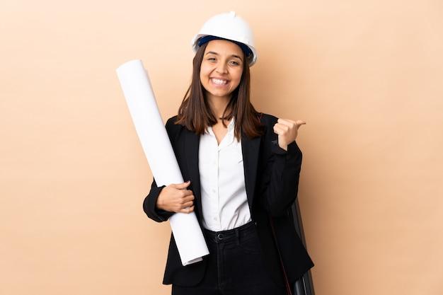 Молодой архитектор женщина, держащая чертежи на изолированной стене с недурно жест и улыбается