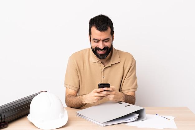 携帯電話でメッセージを送信するテーブルのひげを持つ白人建築家男