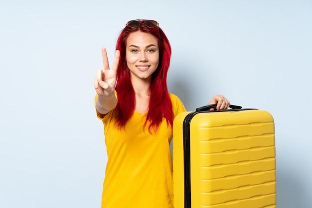 Женщина путешественника держа чемодан изолированный на голубой стене усмехаясь и показывая знак победы