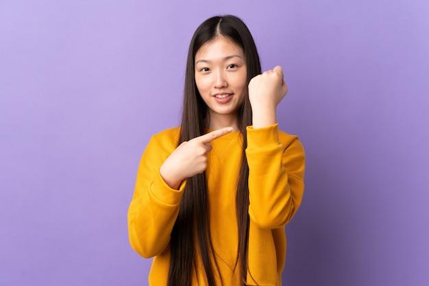 Молодая китайская женщина над изолированной фиолетовой стеной делая жест опоздания