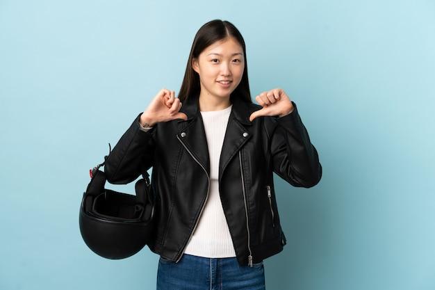 中国の女性が誇りと自己満足の孤立した青い壁にオートバイのヘルメットをかざす