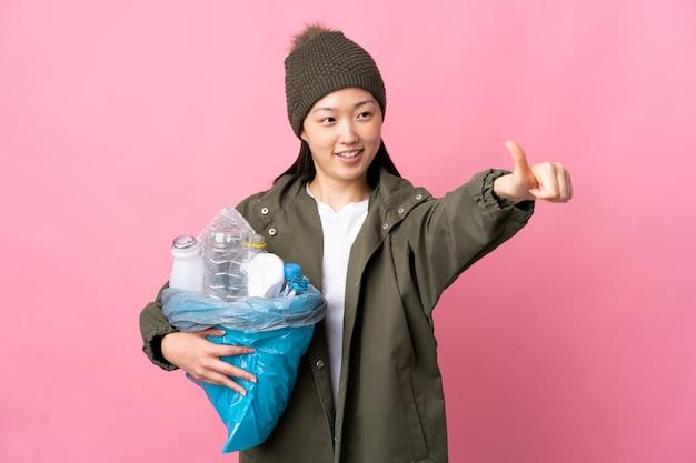 中国の女性が親指を立てるジェスチャーを与える孤立したピンクの壁を越えてリサイクルするペットボトルの完全な袋を保持しています。