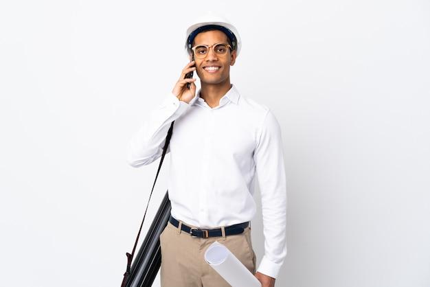 ヘルメットと孤立した白い壁に青写真を保持しているアフリカ系アメリカ人の建築家の男_誰かと携帯電話で会話を続ける