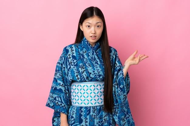 Кимоно молодой китайской женщины нося над изолированной стеной делая жест сомнений