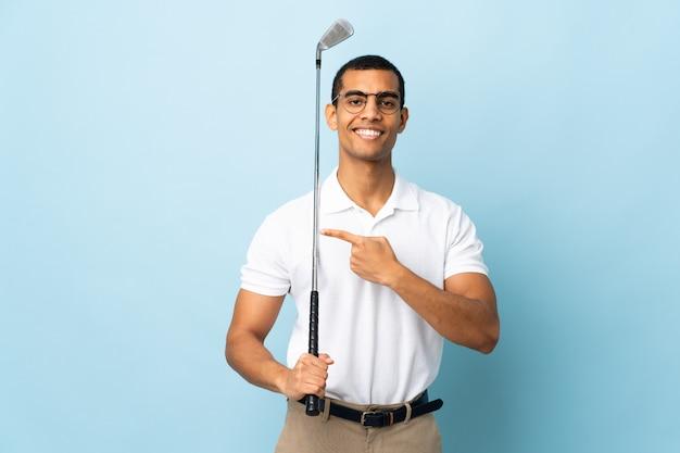 ゴルフを分離し、側面を指している孤立した青い壁にアフリカ系アメリカ人の男