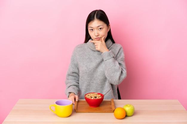 Молодая китайская женщина завтракает в таблице мышления