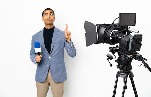 Репортер афроамериканец мужчина держит микрофон и сообщать новости по изолированной белой стене с скрестив пальцы и желая лучшего