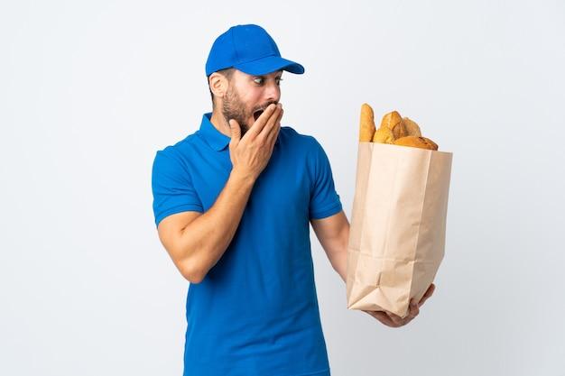 驚きとショックを受けた表情で白い壁に分離されたパンの完全な袋を保持している配達人