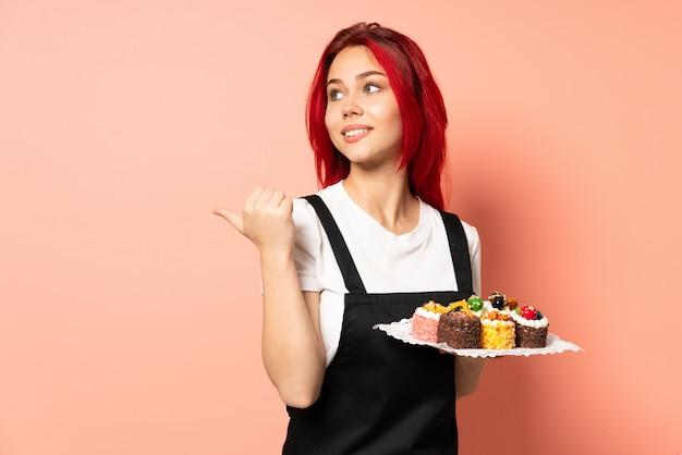 Шеф-кондитер держит кексы, изолированные на розовой стене, указывая в сторону, чтобы представить продукт
