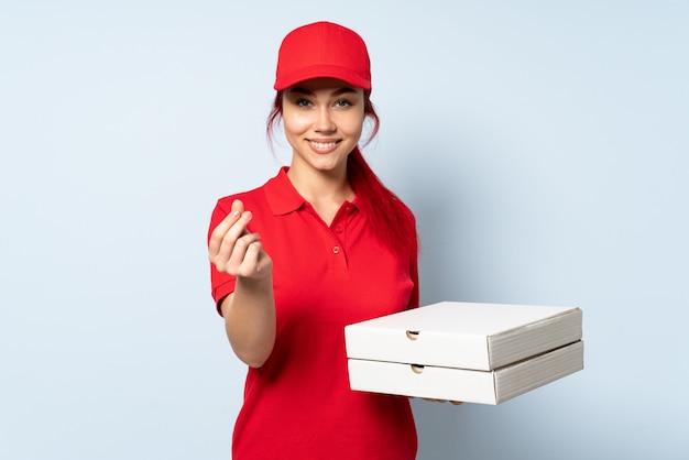 お金のジェスチャーを作る孤立した壁にピザを置くピザ配達女性