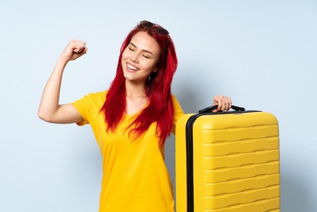 Путешественник женщина, держащая чемодан, изолированных на синей стене, празднует победу