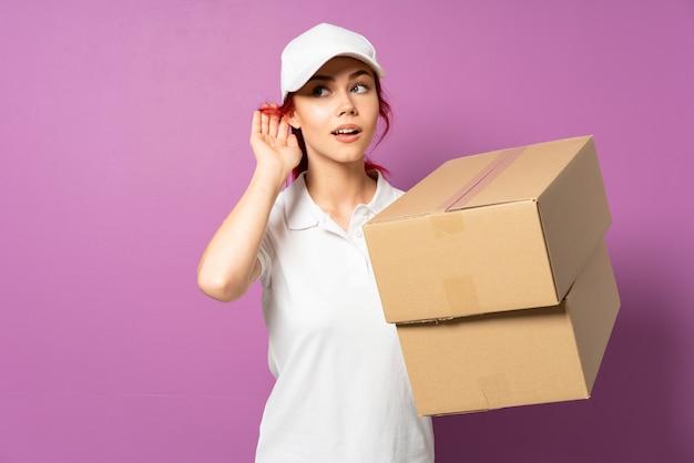 Девочка доставки подростка, изолированные на фиолетовый, слушая что-то, положив руку на ухо