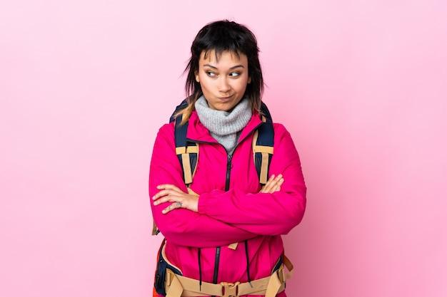 Молодая девушка альпиниста с большим рюкзаком на изолированных розовый мышления идея