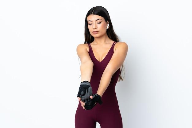 Молодая женщина спорта над изолированной белой протягивая рукой