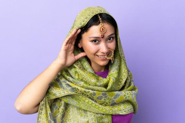 Индийская женщина, изолированные на фиолетовый, слушая что-то, положив руку на ухо