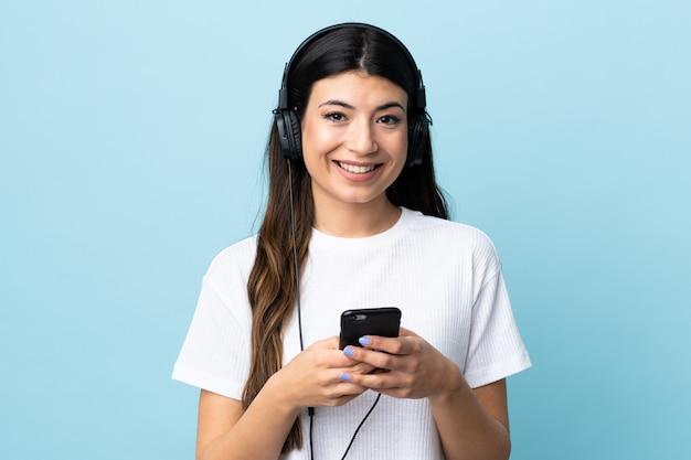 Молодая девушка брюнет над изолированной голубой слушая музыкой с чернью и смотрящ фронт