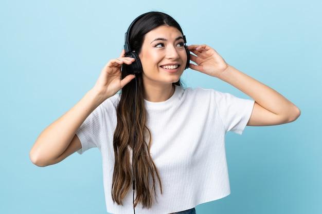 Молодая девушка брюнет над изолированной голубой слушая музыкой и петь