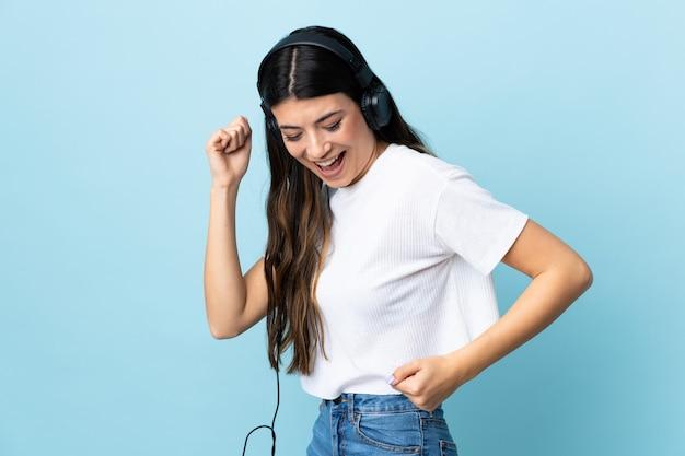 Молодая девушка брюнет над изолированной голубой слушая музыкой и танцами