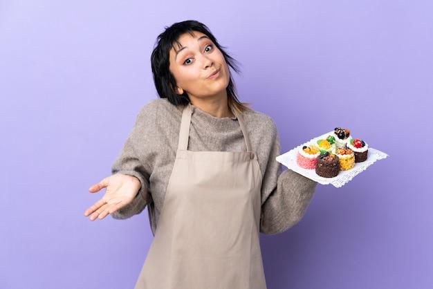 Молодая женщина, держащая много различных мини-пирожных над изолированных фиолетовый, имеющие сомнения с выражением лица путать
