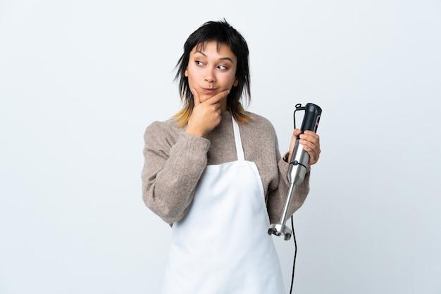 Девушка шеф-повара используя ручной блендер над изолированной белизной думая идея