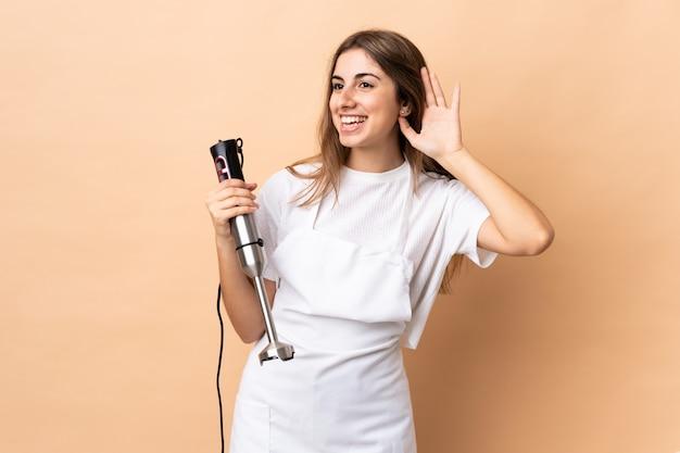 Женщина, используя ручной блендер над изолированным, слушая что-то, положив руку на ухо