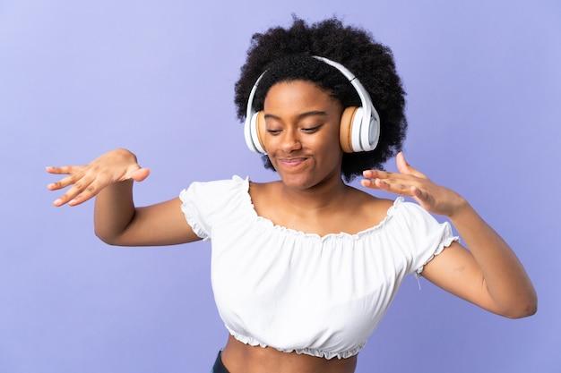 Молодая женщина, изолированные на фиолетовый прослушивания музыки и танцев