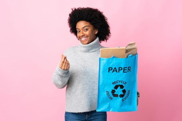 Молодая женщина, держащая рециркуляции мешок, изолированные на красочные зарабатывать деньги жест