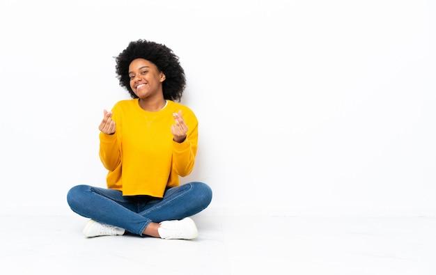 Молодая женщина, сидя на полу, делая деньги жест