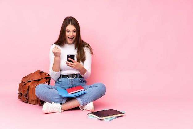 Девушка студента подростка кавказская сидя на изолированном поле на пинке удивленная и посылая сообщение