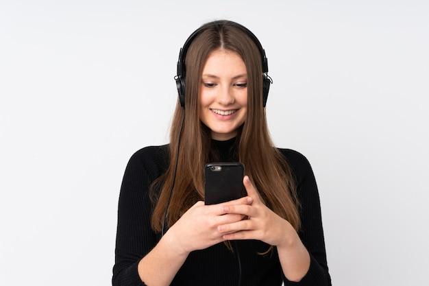 Девушка подростка кавказская изолированная на белой слушая музыке и смотря к черни