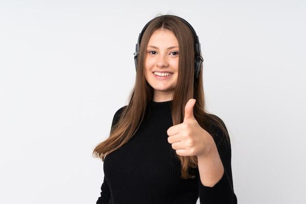 Девушка подростка кавказская изолированная на белой слушая музыке и с большим пальцем руки вверх