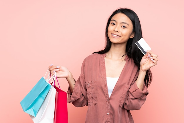 買い物袋とクレジットカードを保持しているピンクに分離されたティーンエイジャーの女の子