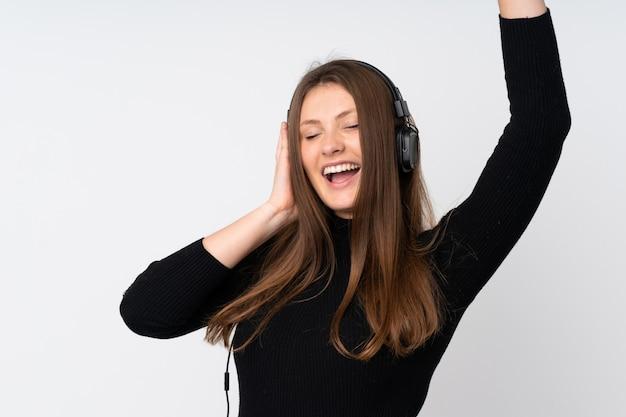 Девушка подростка кавказская изолированная на белых слушая музыке и танцах