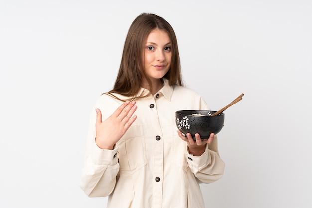 Девушка подростка кавказская изолированная на белизне приглашая прийти с рукой. рад, что вы пришли, держа миску лапши с палочками для еды