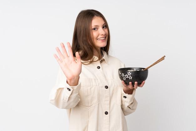 Девушка подростка кавказская изолированная на белизне салютуя с рукой с счастливым выражением пока держащ миску лапши с палочками для еды